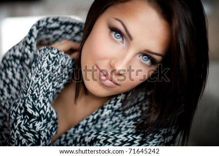 Close up of a beautiful blue-eyed girl in warm sweater - stock photo
