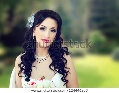 close up of a beautiful bride in the park - stock photo