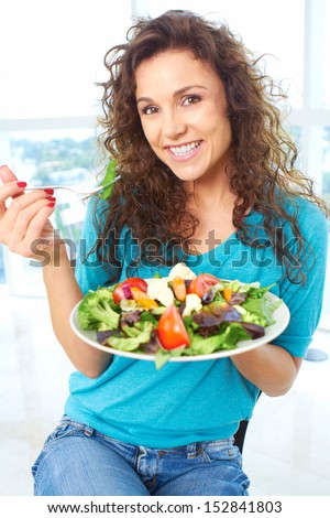 Close-up of a beautiful happy female eating a salad - stock photo