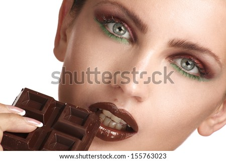 close up of a beautiful model tasting dark chocolate on white - stock photo