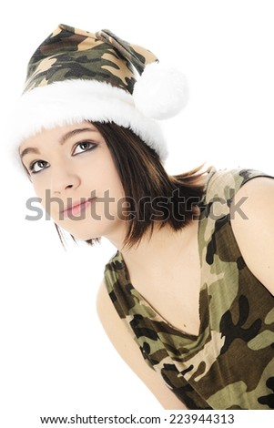 Close-up of a beautiful teen girl looking up.  She's dressed in a camouflage Santa hat and sleeveless shirt.  On a white background. - stock photo