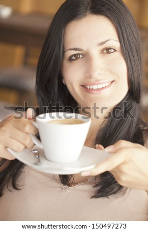 Close up of a beautiful woman offering you a cup of coffee - stock photo