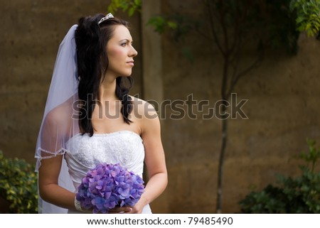Close up of a beautiful young bride with purple bouquet - stock photo