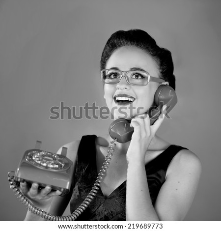 Close up of a beautiful young girl with yellow glasses using an old green phone smiling expression in black and white - stock photo