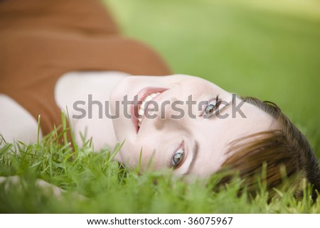 Close-up of a beautiful young woman lying down of grass - stock photo