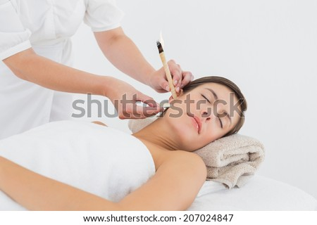 Close up of a beautiful young woman receiving ear candle treatment at spa center - stock photo