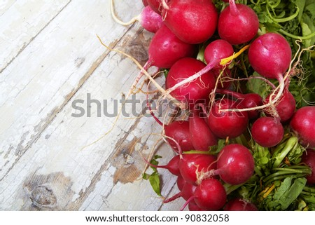 Close-up of a big bunch of fresh radish on grunge wooden background. - stock photo