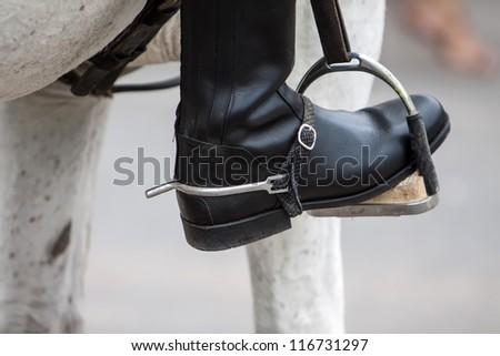 close up of a black leather boot on stirrup - stock photo