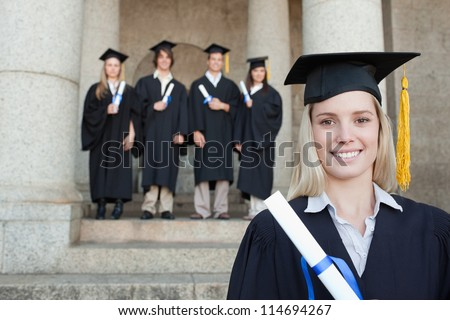Close-up of a blonde graduate with her friends in background in front of the university - stock photo
