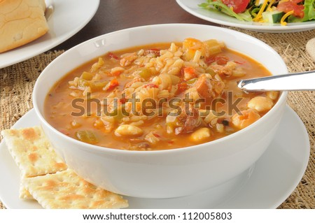 Close up of a bowl of chicken gumbo with a salad and dinner rolls - stock photo