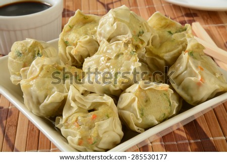 Close up of a bowl of Chicken Shu Mai with soy sauce - stock photo