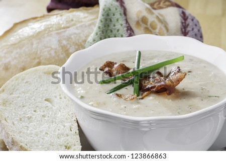 close up of a bowl of seafood soup with bacon and chives garnish and rustic loaf of bread - stock photo