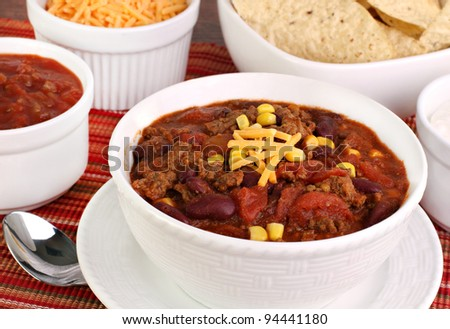 Close up of a bowl of taco soup surrounded with condiments. - stock photo