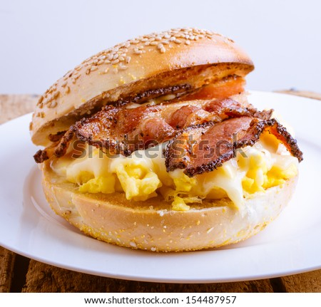 Close up of a breakfast sandwich of toasted sesame bagel, slab bacon, egg and melted cheese. - stock photo