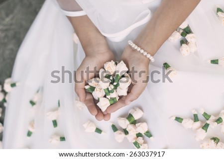 Close up of a bride or a girl doing her first holy communion holding small rose buds. Vintage, washed out look, soft filter - stock photo