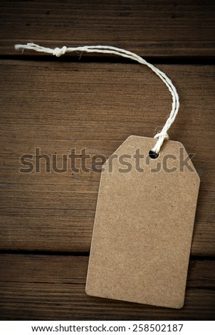 Close Up Of A Brown Label With White Ribbon On Wooden Background For Copy Space Or Free Text Or Your Text Here Frame And Vintage Or Retro Style Vertical Format - stock photo