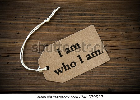 Close Up Of A Brown Label With White Ribbon On Wooden Background With English Life Quote I Am Who I Am Frame And Vintage Or Retro Style - stock photo