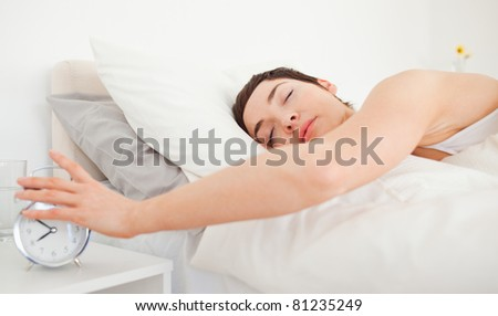 Close up of a brunette turning off her alarm clock in her bedroom - stock photo