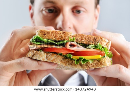 Close up of a business man eating a healthy ham, cheese, tomato sandwich, selective focus on food - stock photo