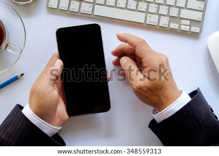 Close up of a business man using mobile smart phone. - stock photo