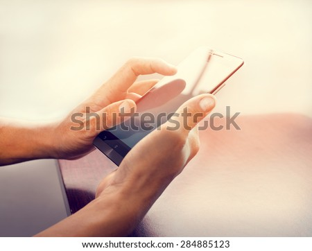 Close up of a business man using mobile smart phone   at wooden table with retro instagram filter effect  - stock photo