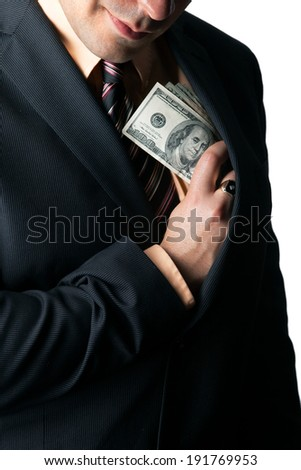 Close up of a business mans hand hiding money in his suit jacket pocket and a smirk on his face. - stock photo