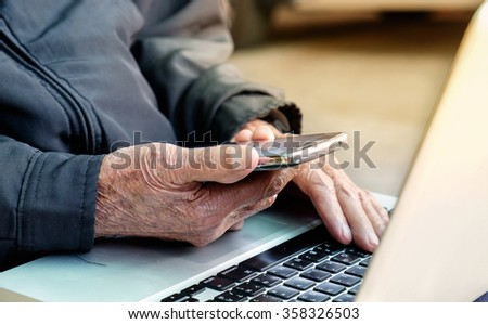 Close up of a business old man using mobile smart phone and laptop - stock photo