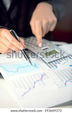 Close up of a business woman calculating. - stock photo