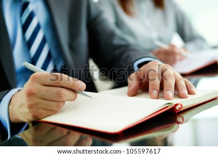 Close-up of a business worker with a blank notebook - stock photo