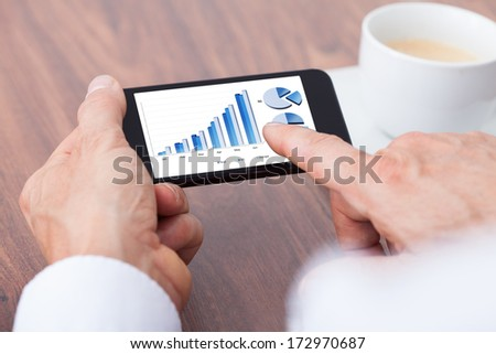 Close-up Of A Businessman Analyzing Graph On Smartphone - stock photo