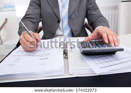 Close-up Of A Businessman Calculating Bills Using Calculator - stock photo