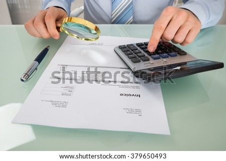 Close-up Of A Businessman Checking Invoice With Magnifying Glass And Calculator - stock photo