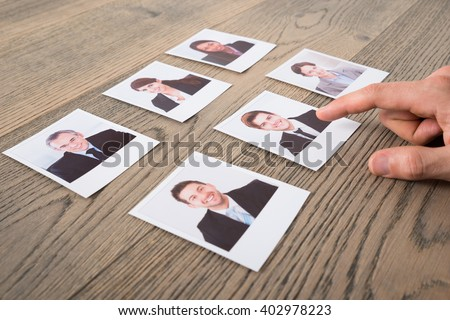 Close-up Of A Businessman Choosing Candidates At Desk In Office - stock photo