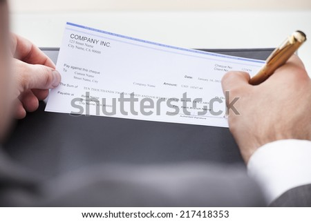 Close-up Of A Businessman Filling Blank Cheque - stock photo