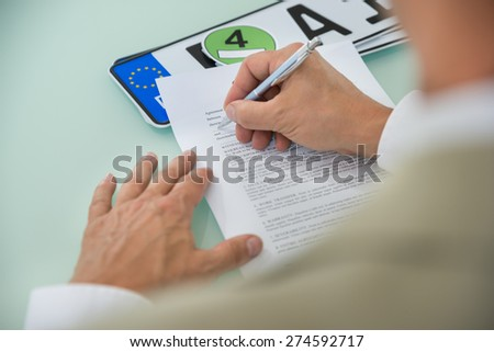 Close-up Of A Businessman Filling Car Sale Contract Form With Vehicle Registration Plate On Desk. Contract Paper Contains Placeholder Text - stock photo