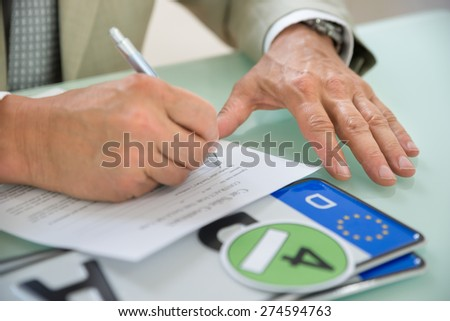 Close-up Of A Businessman Filling Car Sale Contract With Number Plate On Desk. Contract Paper Contains Placeholder Text - stock photo