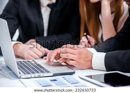 Close-up of a businessman hands working behind the laptop. Businesspeople sitting at a table at a meeting in the office. - stock photo