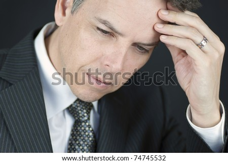Close-up of a businessman holding his head in his hand. - stock photo