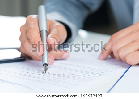 Close Up Of A Businessman Holding Pen On A Document - stock photo