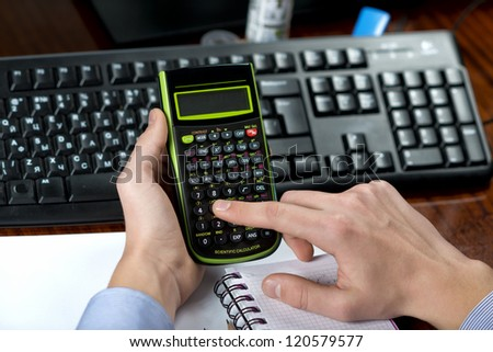 Close-up of a businessman in office with calculator says - stock photo