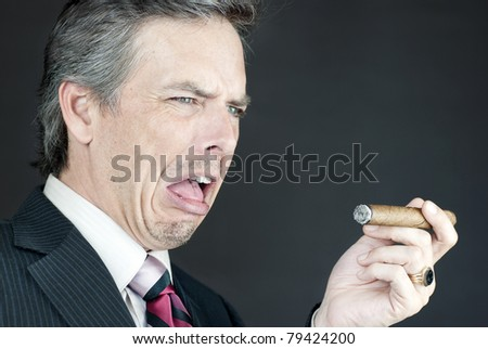 Close-up of a businessman looking at a cigar in disgust. - stock photo
