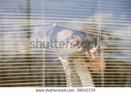 Close-up of a businessman looking through a window - stock photo