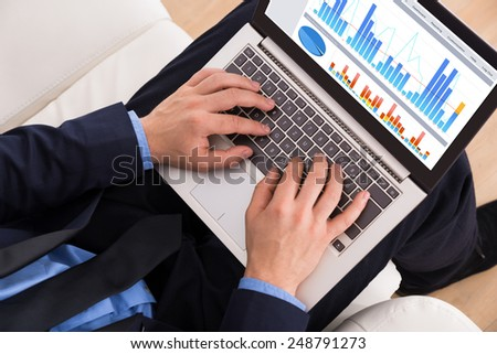Close-up Of A Businessman On Couch Analyzing Graph On Laptop - stock photo