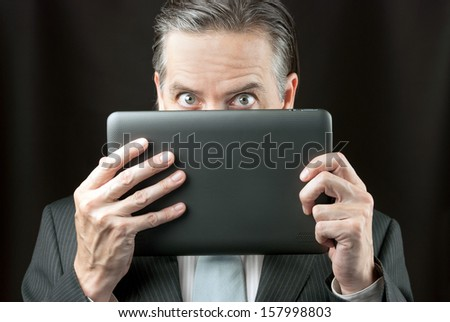Close-up of a businessman peeking over his tablet - stock photo