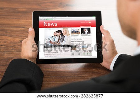 Close-up Of A Businessman Reading Online News On Digital Tablet - stock photo