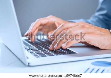 Close Up Of A Businessman's Hand On Laptop Keypad - stock photo