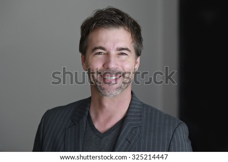 Close up OF A Businessman Smiling At The Camera - stock photo
