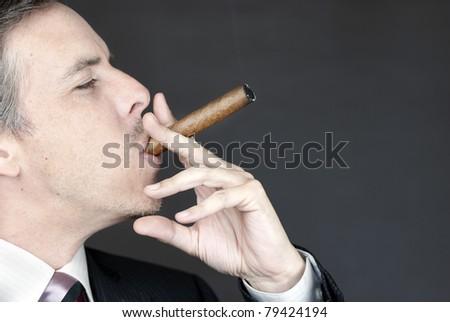 Close-up of a businessman smoking a cigar appreciatively. - stock photo