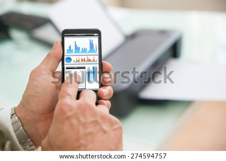 Close-up Of A Businessman Using Cellphone For Printing Graph Paper. Photographer owns copyright for images on screen - stock photo