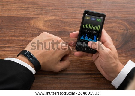 Close-up Of A Businessman With Smart Wristband And Cellphone Showing Fitness Stats - stock photo